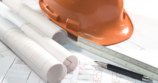 Casque de chantier sur des plans d'architecte