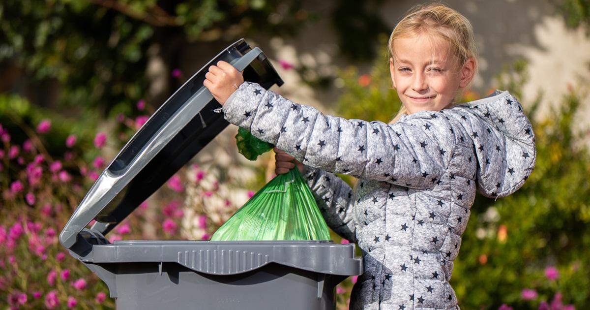 Fille qui jette un sac dans une poubelle grise