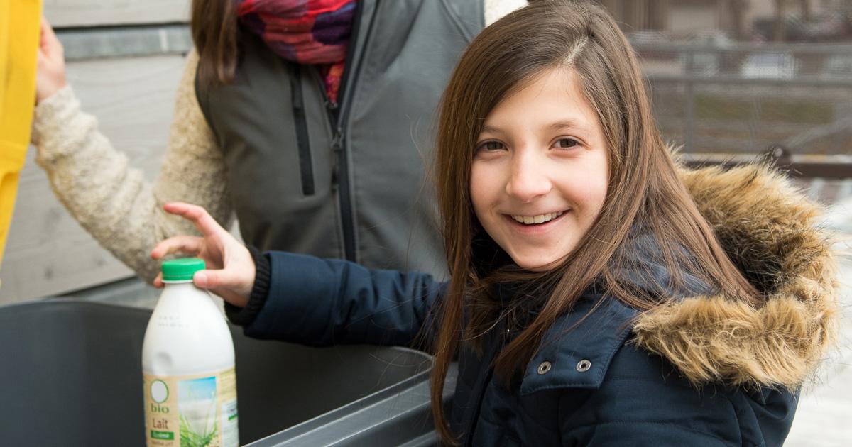 Fille qui jette une bouteille plastique dans un bac jaune
